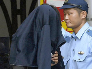 ジャンパーで顔を隠して警察署を出る容疑者