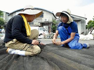 エリの網に開いた穴を直す手ほどきを受ける31歳の見習い漁師