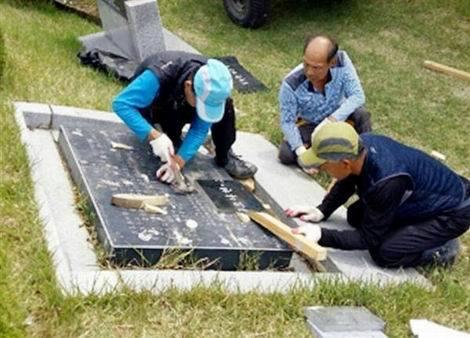 奥氏が張り付けた「慰霊の石板」を引き剥がす作業員ら(470x338)